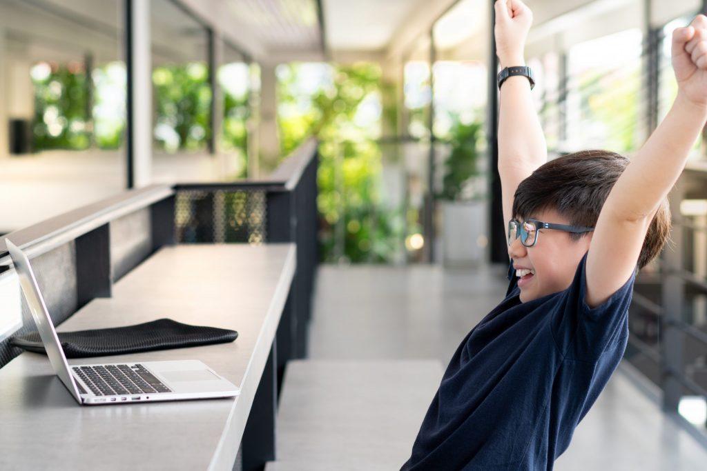 un estudiant celebrant que resol un problema a la seva classe de programació on-line.